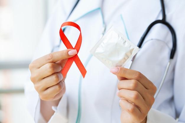 安全なセックスとエイズからの保護を求める赤いリボンとコンドームを持っている医師 Premium写真