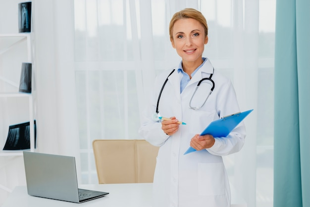 Doctor holding clipboard looking at camera Premium Photo