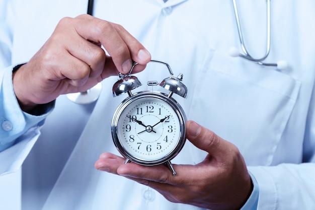 Doctor holding a clock Premium Photo