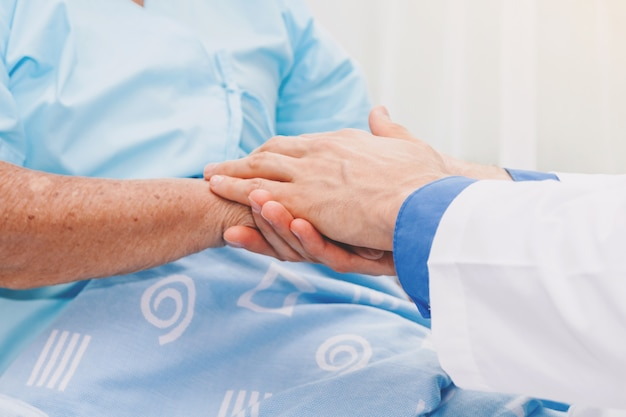 Doctor holding elderly person hand with care in hospital.healthcare and medicine Premium Photo