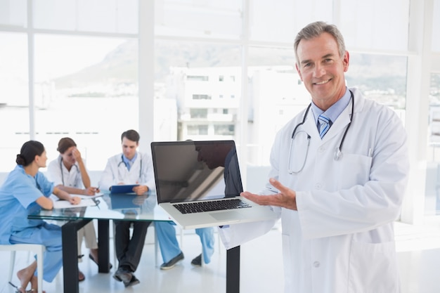 Doctor holding laptop with group around table in hospital Premium Photo