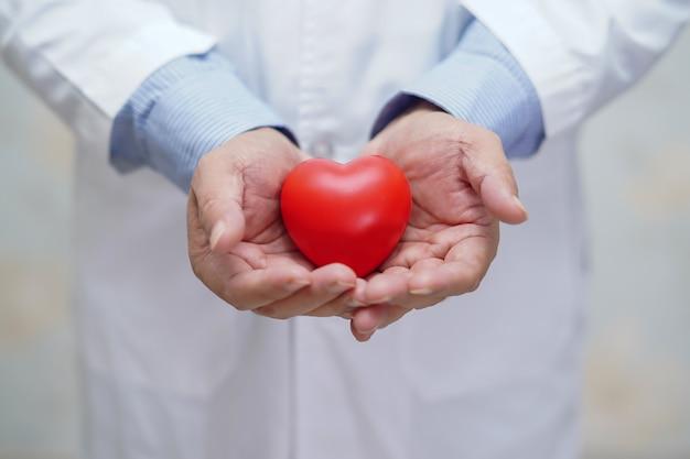 医師が看護病院で彼の手に赤いハートを保持しています。 Premium写真