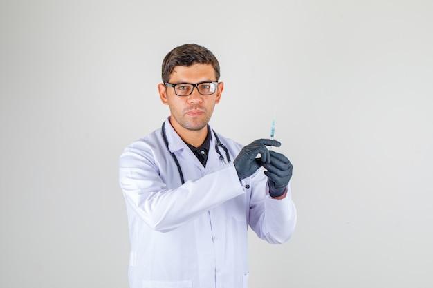 聴診器で白衣のカメラを見ながら医師持株シリンジ 無料写真