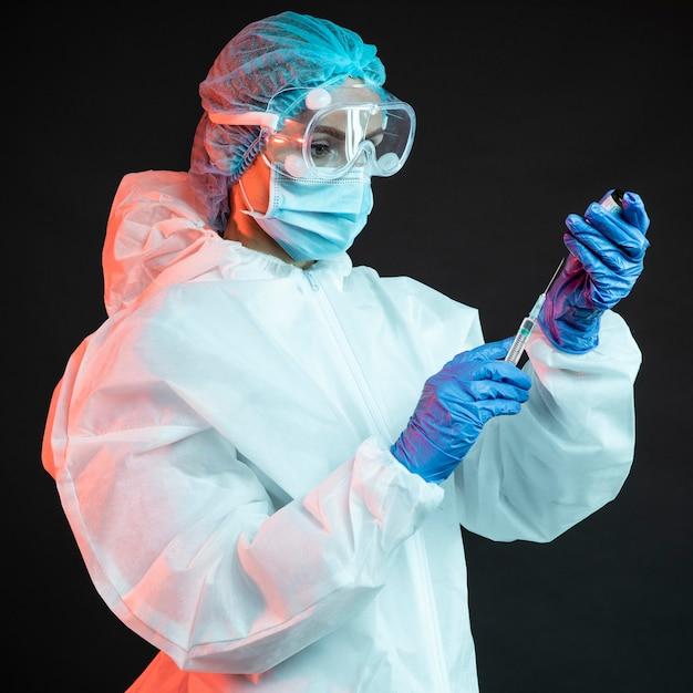 Medico che tiene una siringa mentre indossa una mascherina medica Foto Gratuite