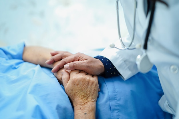 Doctor holding touching hands asian senior or elderly old lady woman patient with love, care. Premium Photo
