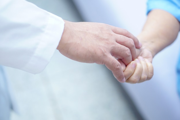 Doctor holding touching hands asian senior or elderly old lady woman patient with love Premium Photo