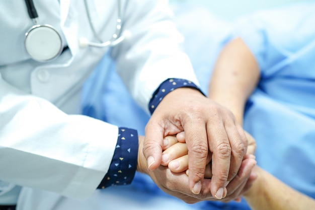 Doctor holding touching hands asian senior old lady woman patient with love, care and empa Premium Photo