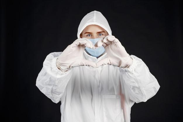 医療用マスクの医者。コロナウイルスのテーマ。白い背景の上に分離されました。防護服を着た女性。 無料写真