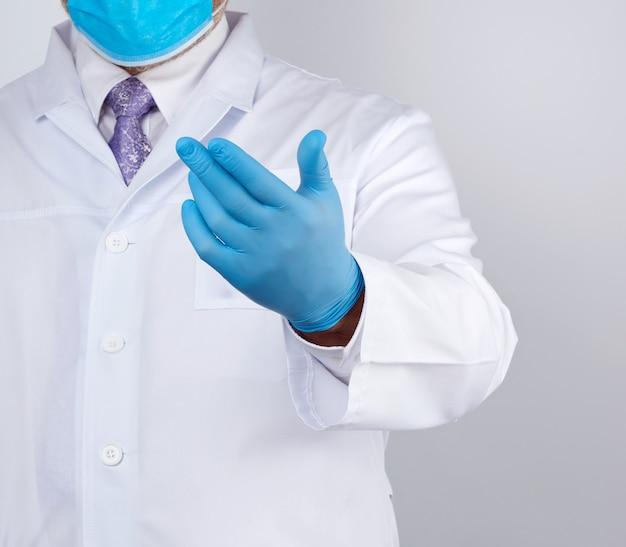 ボタンと青いラテックス手袋の白いコートを着た医者が彼の手を差し出し、招待の概念 Premium写真