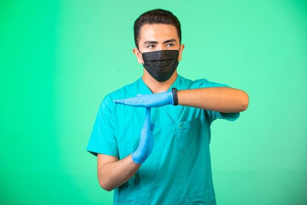 緑色の制服を着た医師とフェイスマスクは、人々に理解してもらうための手振りをします。 無料写真