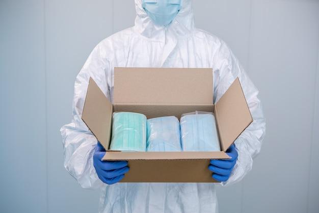 Врач в сиз и медицинской маске открывает коробку и показывает упаковку новых хирургических масок, которые он должен взять с собой во время пандемии covid19. Premium Фотографии