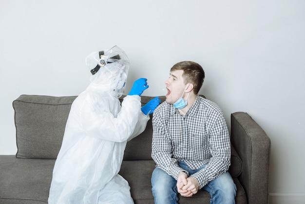 Врач в защитном костюме сиз берет мазок на образец вируса коонавируса covid-19 у пациента Premium Фотографии