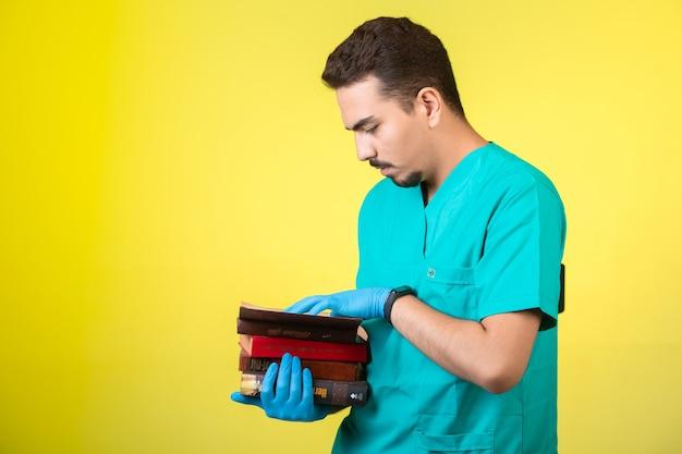 本を押しながら練習している制服とハンドマスクの医師。 無料写真