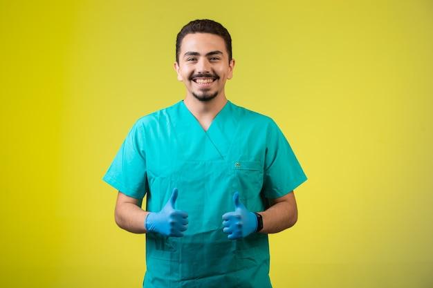 制服を着た医師とハンドマスクは満足し、笑顔で真ん中に立っています。 無料写真