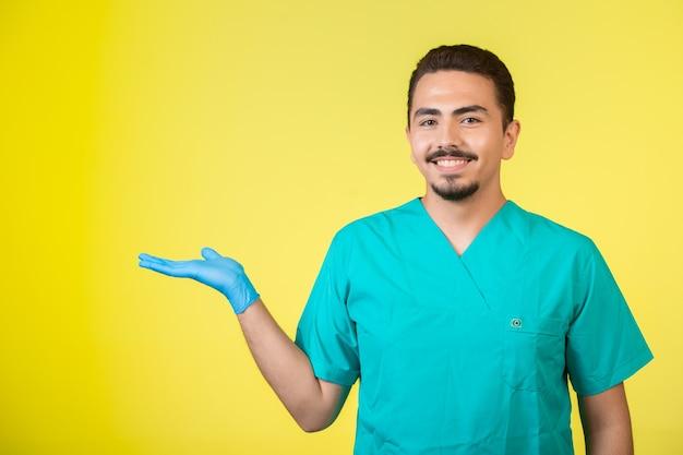 片手が上に開いているユニフォームとハンドマスクの医師。 無料写真