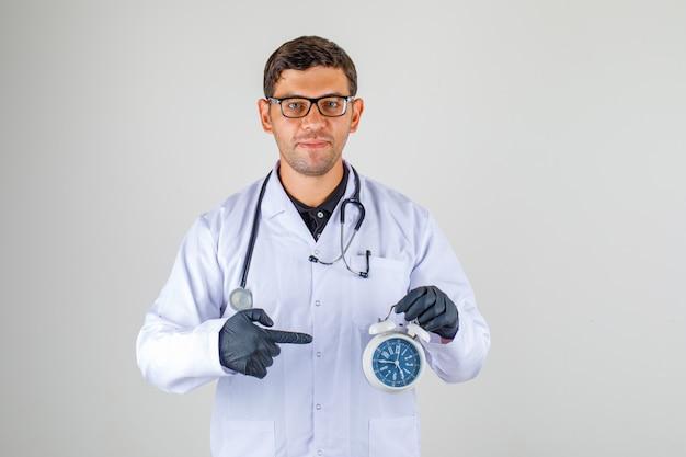 Доктор в белом халате со стетоскопом и будильником Бесплатные Фотографии