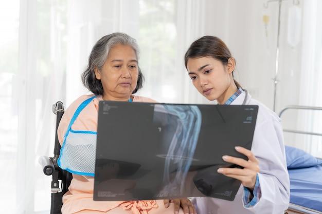 Доктор информ результаты медицинского осмотра рентгеновской пленки для поощрения пожилой пожилой женщины пациенты со сломанной рукой в больнице - медицинская концепция старшего возраста Бесплатные Фотографии