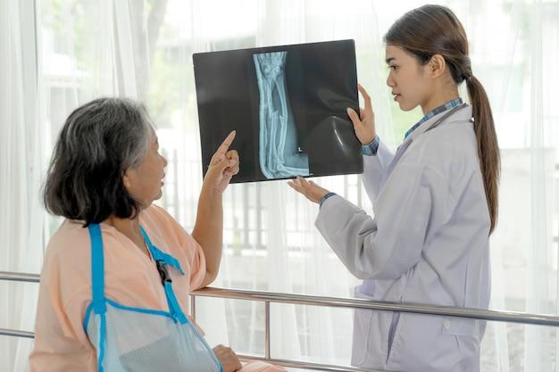 Доктор информ результаты медицинского осмотра рентгеновской пленки, чтобы помочь пожилой женщине пожилым пациентам в больнице Бесплатные Фотографии