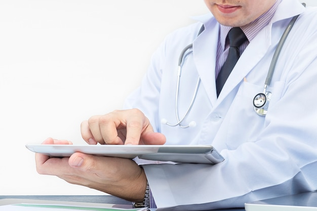 Doctor is working with tablet over white background Free Photo