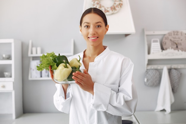 Doctor in a kitchen with vegetables Free Photo
