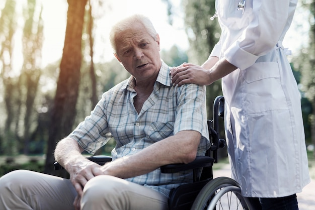 The doctor laid his hand on the sad old man's shoulder Premium Photo