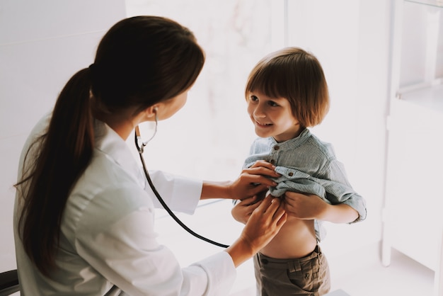 Doctor listening to kids chest with stethoscope Premium Photo