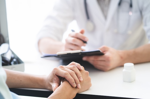 Doctor listening patient explain his symptom and notes to medical record. Premium Photo