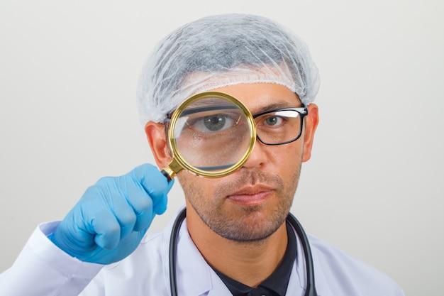 白いコートと帽子で虫眼鏡を通して見る医師 無料写真