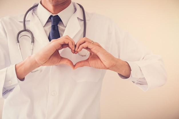 Doctor making his hands in heart shape, heart health,  health insurance concept Premium Photo