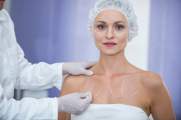 Doctor marking female patients body for breast surgery Free Photo