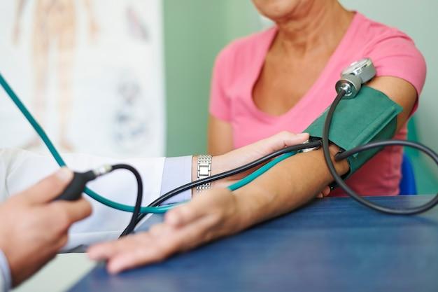 Врач измеряет давление у пожилого пациента Бесплатные Фотографии