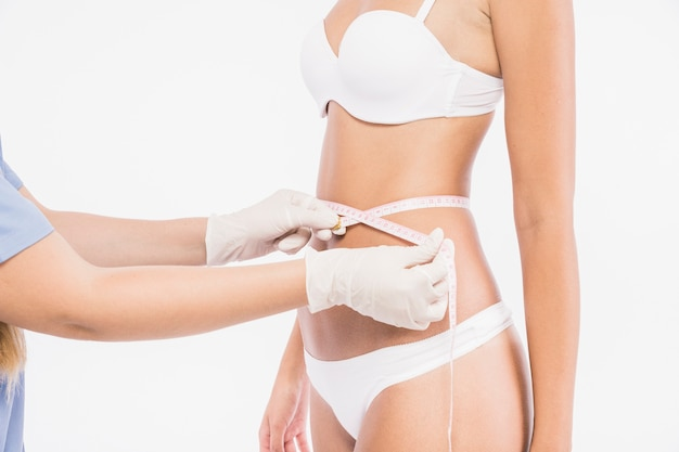 Doctor measuring woman waist Free Photo