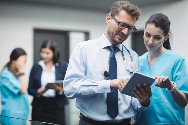 Medico e infermiere discutendo su tavoletta digitale Foto Gratuite