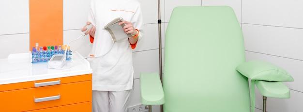 Doctor or nurse holding digital blood pressure gauge in modern hospital room Premium Photo