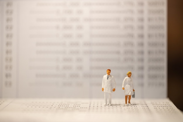 Doctor and nurse miniature figure standing on bank passbook with copy space. Premium Photo