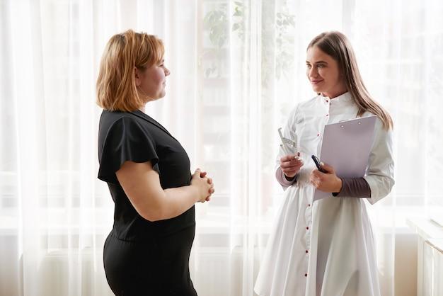 栄養士、栄養士、女性患者が診療所で診察を受けています。若い笑顔 Premium写真