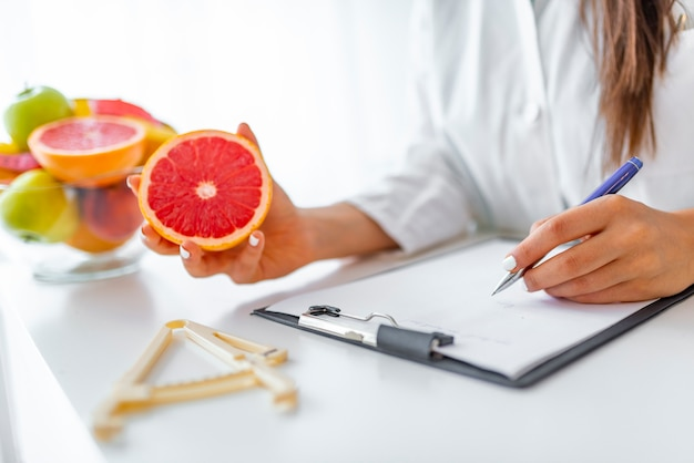 Doctor nutritionist writing case history in the office. Premium Photo
