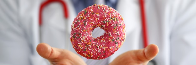 Doctor in office holding in hand pink doughnut closeup Premium Photo