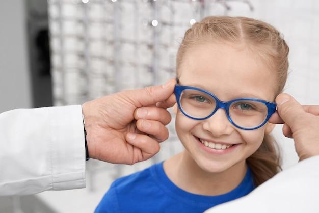 여자 안경을 선택하는 의사 안과 의사. 프리미엄 사진