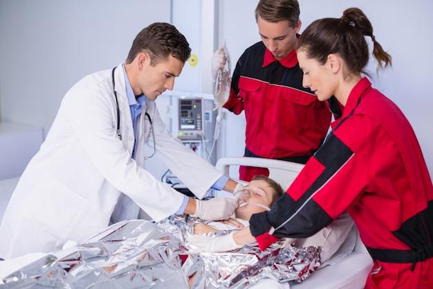 Medico e paramedico che esaminano un paziente in pronto soccorso Foto Gratuite