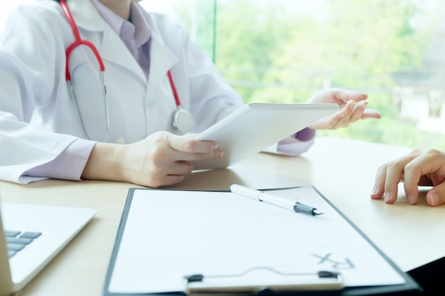 Doctor and patient are discussing something, just hands at the table Free Photo