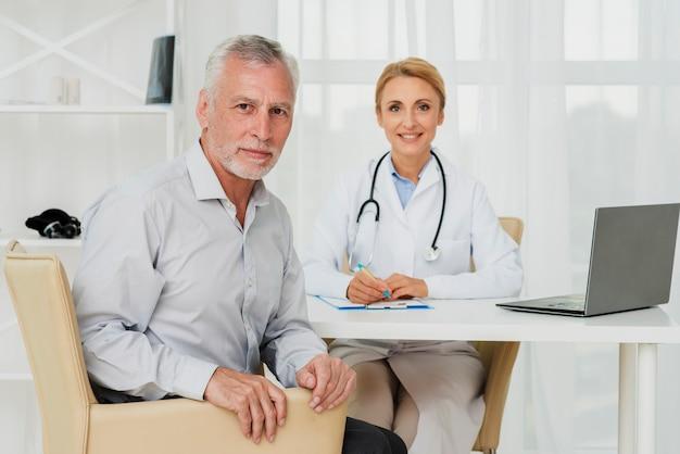 Medico e paziente guardando la fotocamera Foto Gratuite