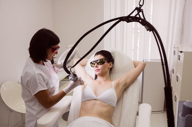 Doctor performing laser hair removal on female patient skin Free Photo