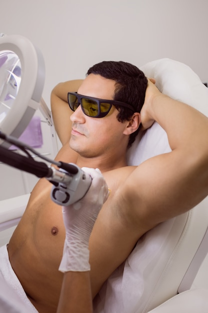Doctor performing laser hair removal on male patient skin Free Photo