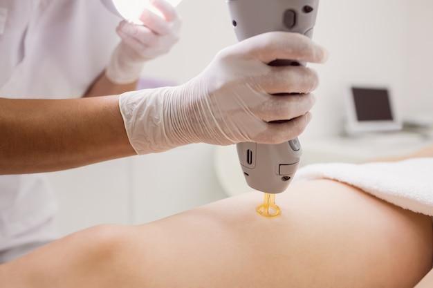 Врач, выполняющий лазерное удаление волос на женской коже пациента в клинике Бесплатные Фотографии