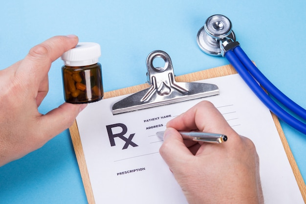 Doctor or pharmacist holding jar or bottle of pills in hand and writing prescription on a special form. medical costs and healthcare payment concept. Premium Photo