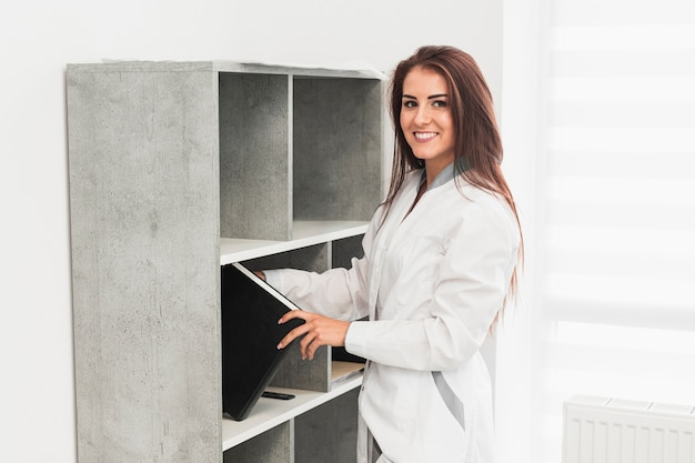 Doctor picking a file from shelf Free Photo
