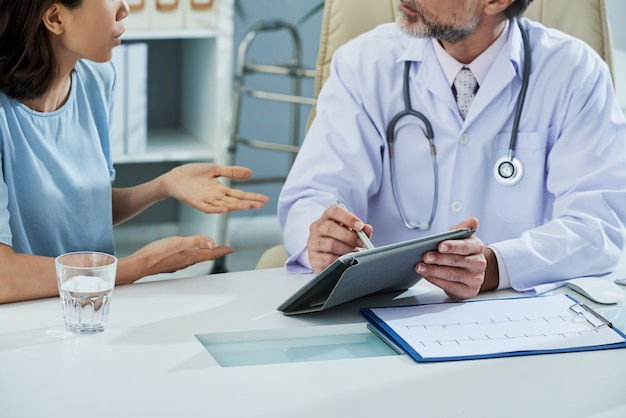 Doctor pointing at digital tablet screen while explaining something to the patient Free Photo