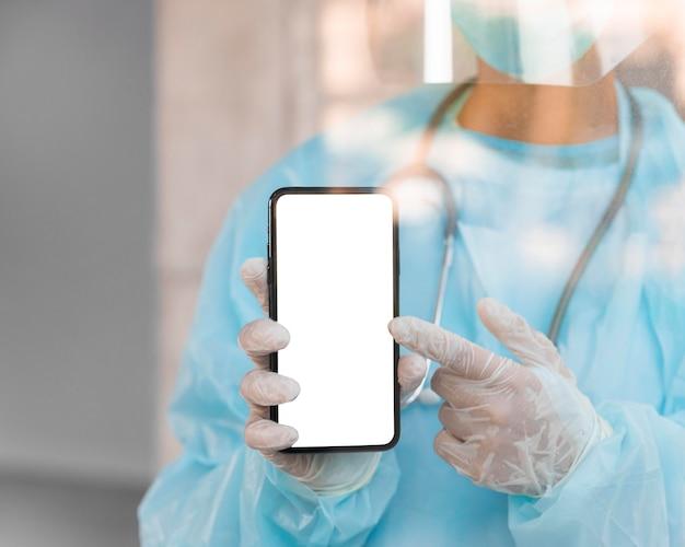 Medico che punta a uno smartphone a schermo vuoto Foto Gratuite