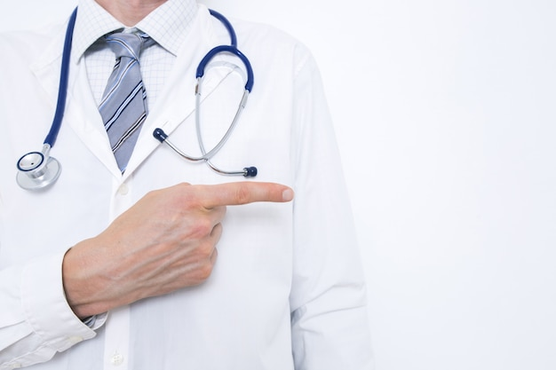 Doctor points in a white coat Premium Photo